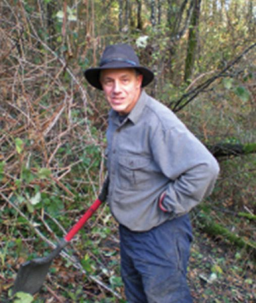 by: PHOTO COURTESY OF CAROLINE SKINNER  - Volunteer Patrick Birkle digs out invasive plants at Nob Hill Nature Park in St. Helens.
