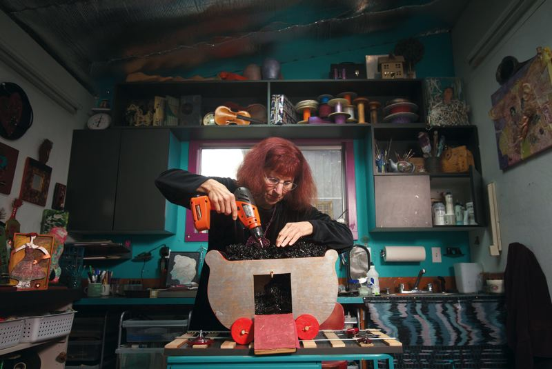 by: JONATHAN HOUSE - PAMPLIN MEDIA - Artist and environmentalist Bonnie Meltzer, top, puts the finishing touches on her work Coal Car, in her North Portland studio. Above, Meltzer knits a fishing line and shells.