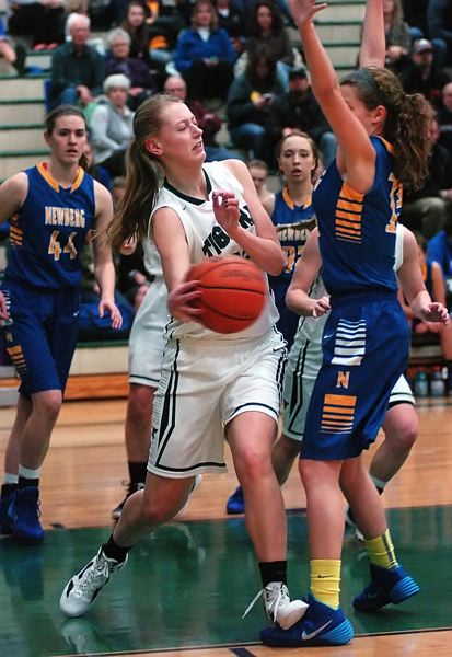 by: DAN BROOD - PASSING FANCY -- Tigard sophomore post Elise Conroy passes the ball around Newberg's Heather Petrie in Friday's game.