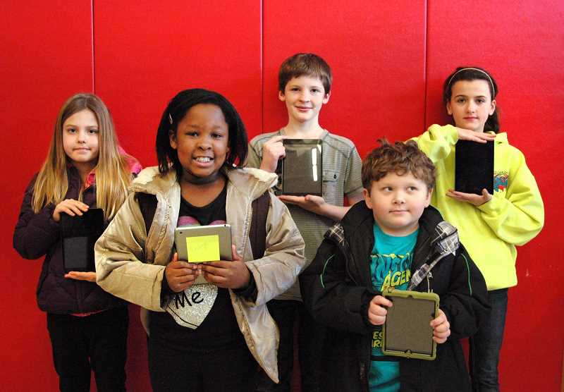by: ISABEL GAUTSCHI - Clackamas River Elementary students show off some of the school's new iPad minis. Students holding iPads include, from left, fourth-grader Katey Carpenter, fourth-grader Ella Gach, sixth-grader Tieran Silver, first-grader Aiden Dolan and sixth-grader Sidnee Keller.