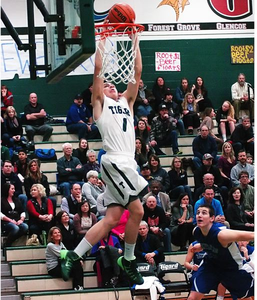 by: DAN BROOD - ABOVE THE RIM -- Tigard High School senior point guard Bryan Berg slams home a dunk off a pass from senior Nick Kaelin in the opening minutes of the Tigers' 88-46 win over Newberg.