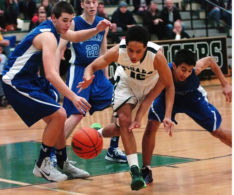 by: DAN BROOD - FIGHTING FOR IT -- Tigard High School senior Elijah Simon (12) battles Newberg's Jacoby Wolfe (left) and BJ Ulloa for the ball during Friday's Pacific Conference opener. Tigard got an 88-46 victory.