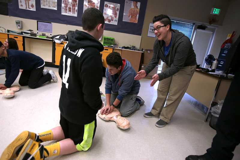 by: TIMES PHOTO: JONATHAN HOUSE - Fowler Middle School health teacher Cindy Pellicci gives pointers to students during a hands-only CPR demonstration from TVF&R. Students in the school will teach five friends and family members how to perform CPR by the end of the year.