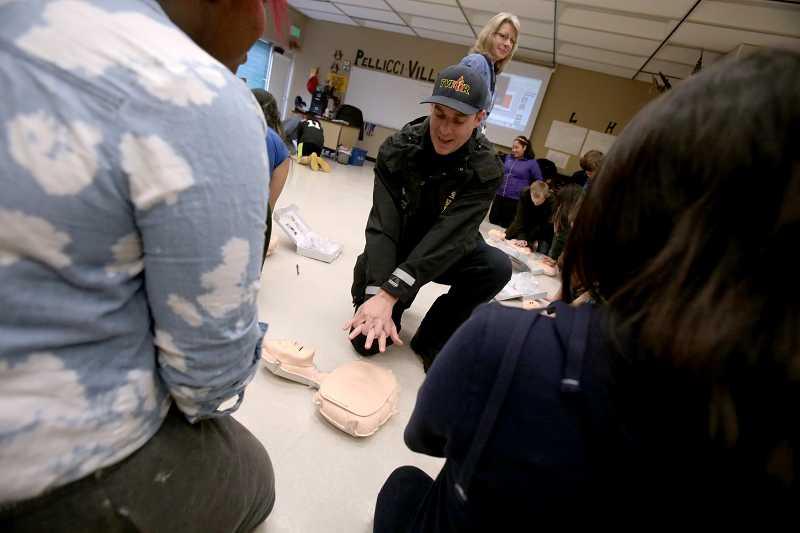 by: TIMES PHOTO: JONATHAN HOUSE - TVF&R firefighter Jason Maurer with Station 50 on Southwest Walnut Street demonstrates proper hands-only CPR technique during a demonstration at Fowler Middle School.