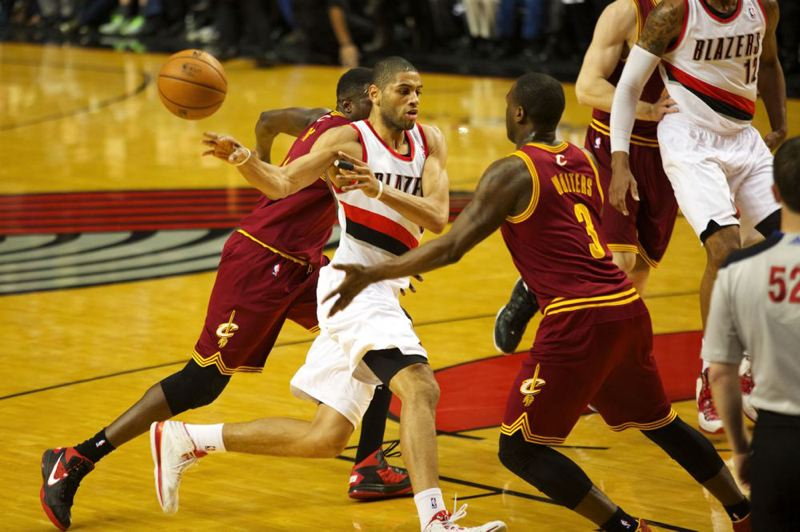 Portland's Nicolas Batum make a no-look as Cavaliers shooting guard Dion Waiters steps up to stop his drive.