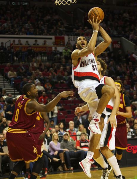 Nicolas Batum twists for a layup against Cleveland guard C.J. Miles (left).