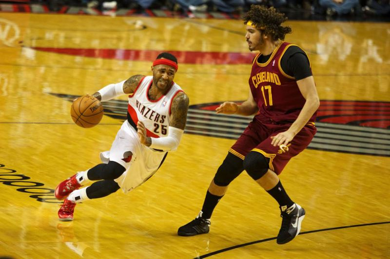 Mo Williams starts a drive to the hoop against Cavaliers center Anderson Varejao.