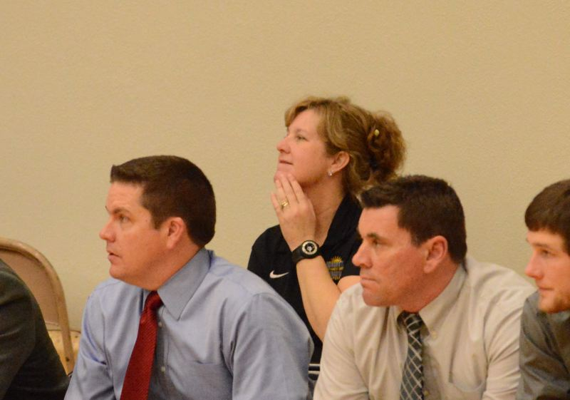 by: JOHN WILLIAM HOWARD - St. Helens Athletic Director Cyndy Miller sits back and watches the action during the boys' basketball game against Liberty on Tuesday evening. Miller will now have to find a new boys' soccer coach, which isn't an easy task.
