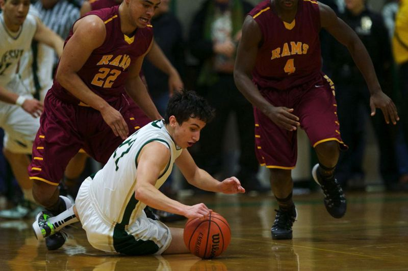 Jesuit's Jack Bell dives for a loose ball as Central Catholic's Cameron Scarlett (left) and LaMar Winston give chase.