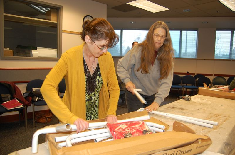 by: PHOTO BY: TOM TRAVER - Jo Ann Wolfe and Jude Watson check frames for fit at the Milwaukie Public Safety Building before other volunteers repack them for storage in case of an emergency.