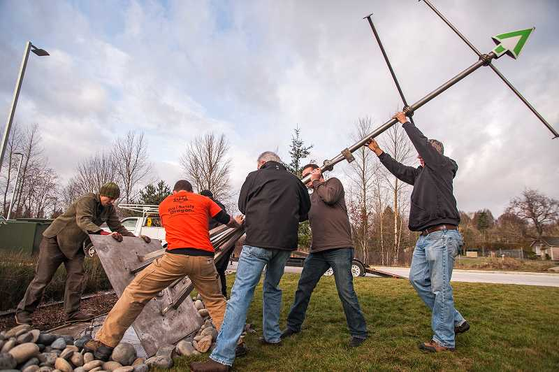 by: SPOKESMAN PHOTO: JOSH KULLA - A 15-foot kinetic sculpture, El Viento, was installed Jan. 13 at SMART headquarters on Boberg Road. The name is Spanish for the wind. Here, sculptor Jesse Swickard, far left, guides Wilsonville Public Works and SMART employees as they mount the piece on a concrete pad.