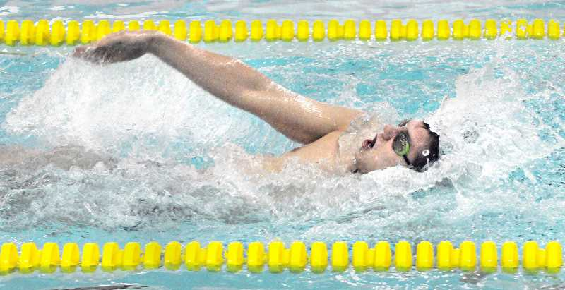 by: SETH GORDON - Making a splash - Senior Bjorn Larsen cruises to first place in the 100 backstroke Jan. 16 versus Forest Grove at the Chehalem Aquatic Center. The Tigers won all 11 events to thrash the Vikings 137-41.