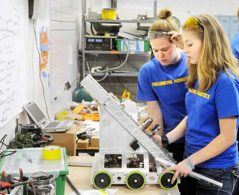 by: SETH GORDON - Iron Men - Jessica Stone and Aurora McCollum work on their robot, Jarvis, at Newberg High School on Friday. Stone and McCollum are two members of the all-girl, all-rookie 'Iron Men' team, which qualified Jan. 11 for the First Tech Challenge robotics state tournament in their first ever event at OMSI in Portland.