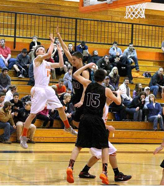 by: CORY MIMMS - Austin Salley takes the shot over Scappoose's defense.