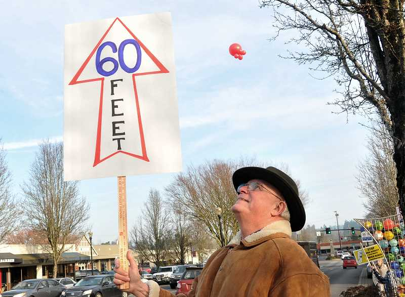 by: VERN UYETAKE - Phil Pirrotta's sign points to a red balloon floating 60 feet above, which Save Our Village says is the maximum height allowed on new construction.