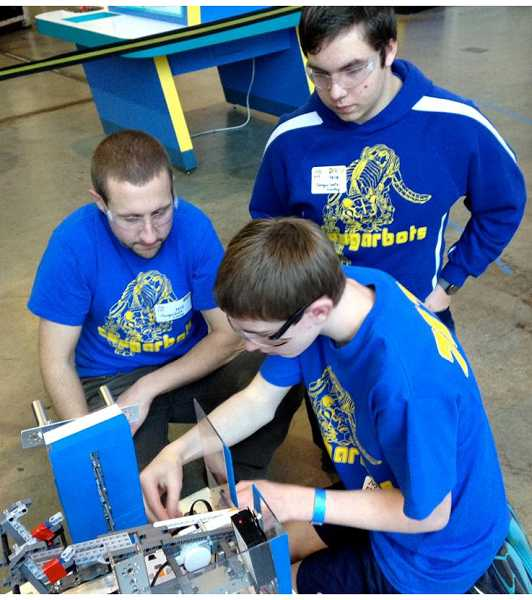 by: SUBMITTED PHOTO - Austin Adair makes adjustments to the team's robot while mentor, Mike Hershberger, left, and teammate Bryce Crispin look on.