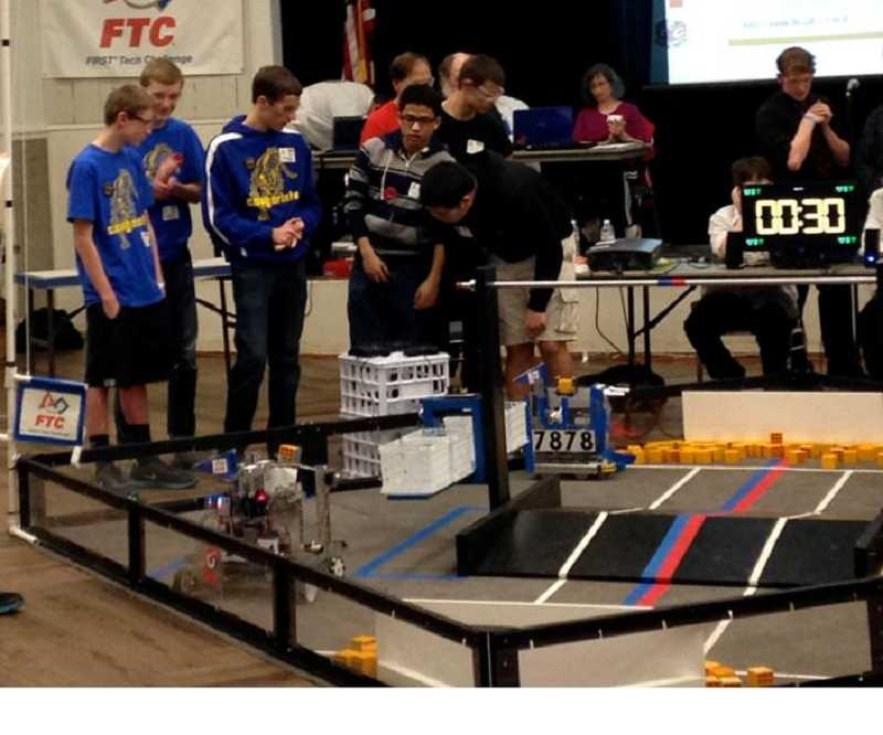 by: SUBMITTED PHOTO - After being chosen to be in the elimination rounds, the Cougarbots and a team from Central Catholic strategize about how to work together, playing both offense and defense, to win the final match.