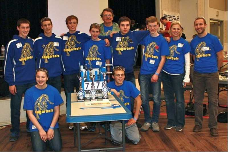 by: SUBMITTED PHOTO - The Cougarbots, mentors and coaches gathers around the robot and trophies after the tournament. They are: (far back) Randy Prakken, mentor, (from left) Ryan Bigej, Ian Oakes, Ben Thompson, Austin Adair, Bryce Crispin, Steven Morris, Jennifer Gingerich, Mike Hershberger, (kneeling front) Madilynn Nissly and Harrison Gingerich