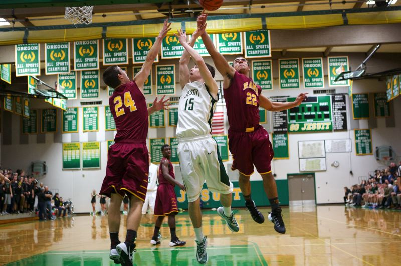 by: TIMES PHOTO: JAMIE VALDEZ - Jesuit junior point guard Reid Bucy puts up a layup attempt over the Central Catholic defense.