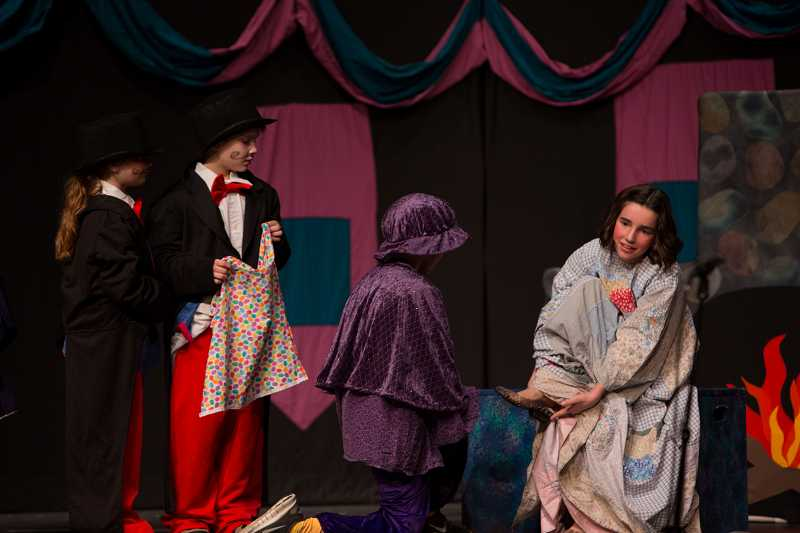 by: SUBMITTED PHOTO: LIONEL COLEMAN - Town criers, from left, Grace Skillern and Zachary Jett stand by as the prince, Jack Bignell, finds the right foot for a lost slipper. Sophie Borah plays the slippers owner, Cinderella.