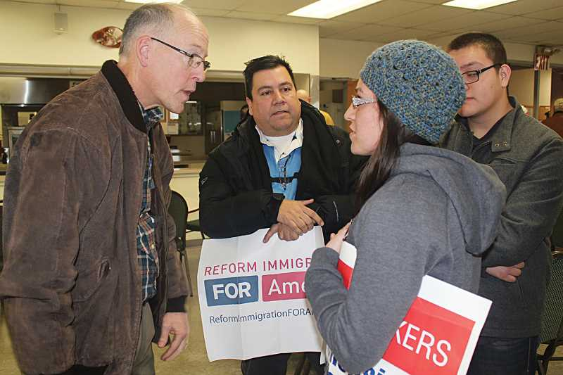 by: HOLLY M. GILL - U.S. Rep. Greg Walden discusses immigration with Sara Ramirez, right, of Madras, and Greg Delgado, of Bend, at a town hall on Monday.