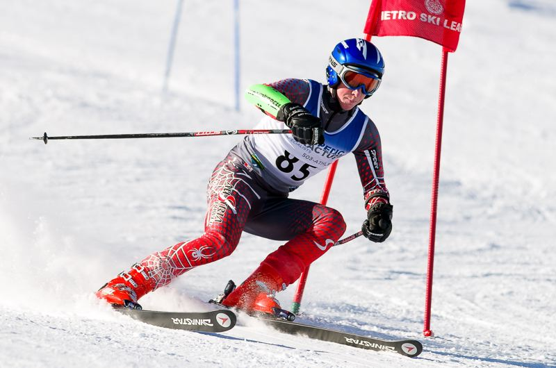 by: MIKE JULIANA PHOTOGRAPHY - MAKING THE TURN -- Tigard's Corey Fusick gets past the gate during Sunday's Metro League giant slalom event.