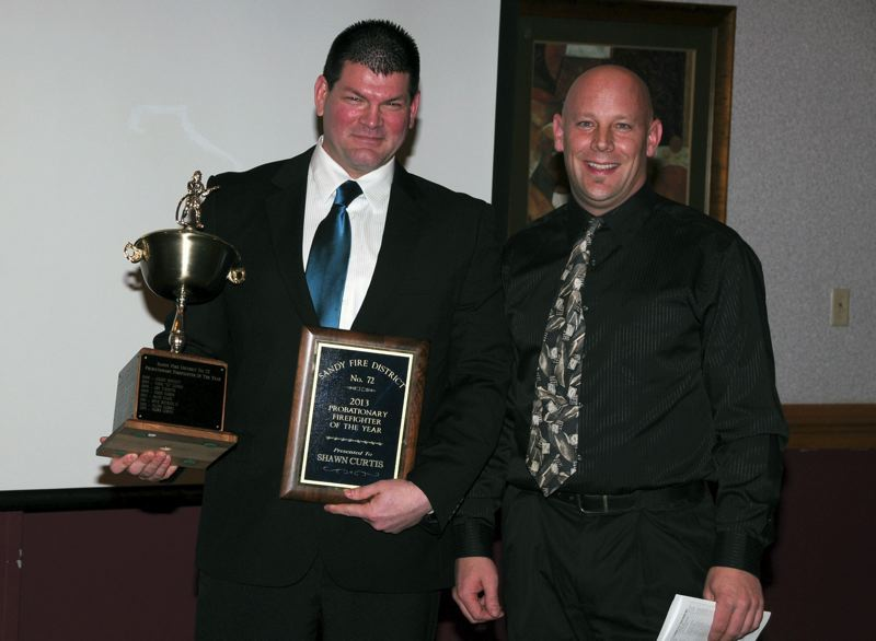 by: COURTESY PHOTO: SANDY FIRE DISTRICT - Firefighter Shawn Curtis, left, receives his award from Capt. Jason McKinnon.