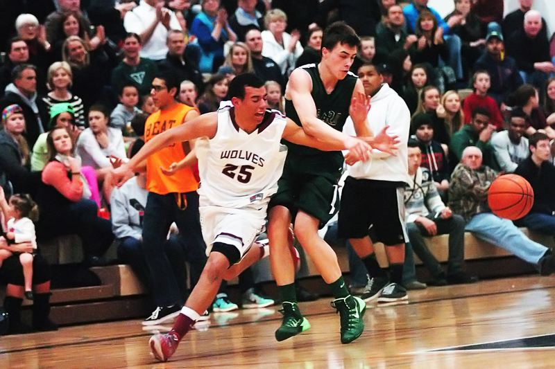 by: DAN BROOD - INTENSITY -- Tualatin junior Alexander Reid (25) and Tigard senior Bryan Berg battle for the ball during Friday's game. Tigard pulled away late in the game to get a 61-54 victory.