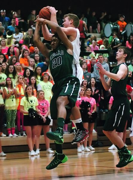by: DAN BROOD - UP FOR GRABS -- Tigard senior Niko Niblack (20) and Tualatin senior Brandon Shroyer battle for a rebound in Friday's game.