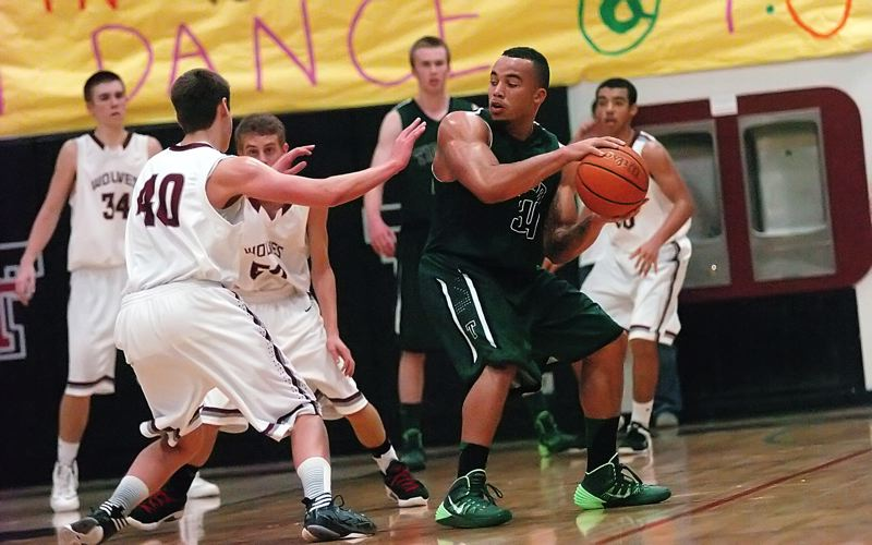 by: DAN BROOD - LOOKING INSIDE -- Tigard senior A.J. Hotchkins (34) looks to get the ball inside against Tualatin seniors Taylor Boos (40) and Joey Fishback in Friday's game. Tigard got a 61-54 win.