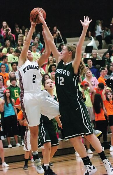 by: DAN BROOD - OUTSTRETCHED -- Tigard sophomore post Elise Conroy (12) challenges a shot by Tualatin senior Jasmine Miller.