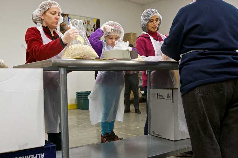 by: TIMES PHOTO: JAIME VALDEZ - Volunteers from Pacific Power, Bank of America, Kaiser Permanente, United Way and Clear Creek Middle School took part in a Day of Service to honor Martin Luther King Jr. by repacking and sorting food at the Oregon Food Bank in Beaverton.