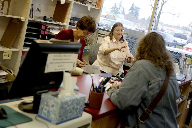by: TIMES PHOTO: JONATHAN HOUSE - Aloha Library volunteers Florence Zeller, left, and Susan Jaeger help a guest at their Farmington Road location. The library plans on moving this spring to a larger storefront in the same shopping center.