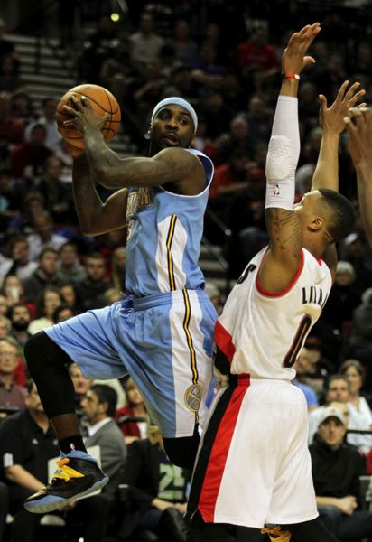Denver's Ty Lawson looks for an open teammate against Damian Lillard.