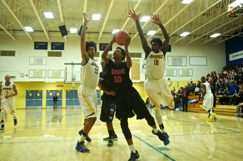 Madison's Myles Fitzgerald-Warren shoots between Jefferson defenders Saudi Edwards (left) and Quintus Hall Jr.