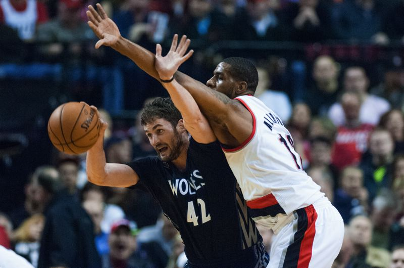 Timberwolves All-Star Kevin Love protects the ball against Blazers All-Star LaMarcus Aldridge.