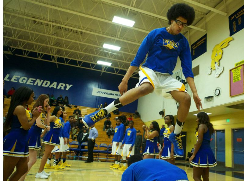 by: TRIBUNE PHOTO: JAIME VALDEZ - Sundi Edwards, Jefferson's 7-foot senior post, leaps over a teammate during the pre-game introductions at Jeff last Friday. The Democrats beat PIl 5A rival Madison 94-61.