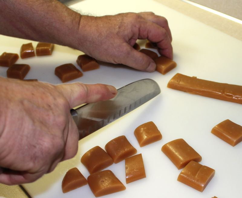by: OUTLOOK PHOTO: ANNE ENDICOTT - Bill cuts his homemade caramels into individual pieces before hand dipping them in a chocolate. Caramels are boxed and sold by the pound for $30.