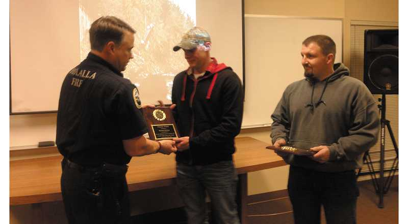 by: PEGGY SAVAGE - Fire Chief Vince Stafford presents a Citizens Award to Michael Holliday and Rick Hendrickson.