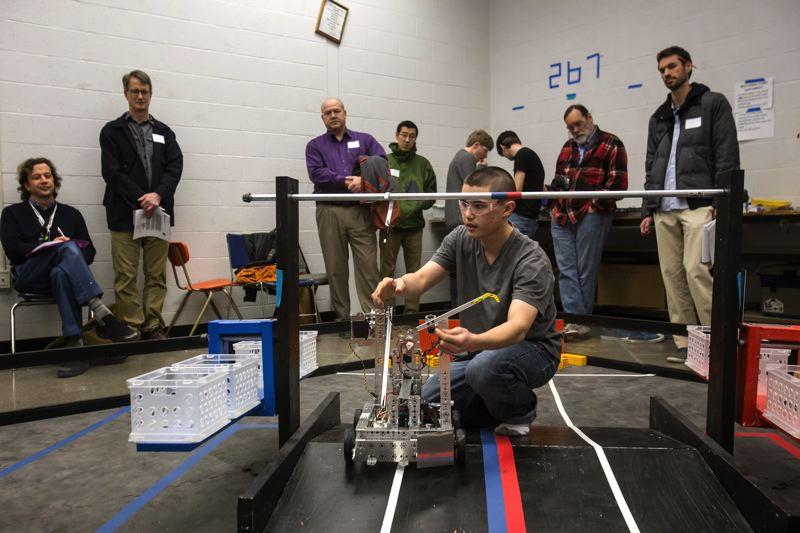 by: TRIBUNE PHOTO: JONATHAN HOUSE - Benson High School Robotics Team member Bronson Kim demonstrates how one of their creations works during an evening tour by parents of prospective students on Monday evening.