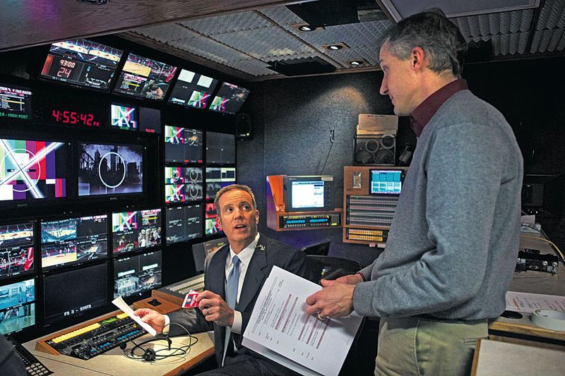 by: TRIBUNE PHOTO: JAIME VALDEZ - Mike Barrett (left) goes over pre-game graphics with his producer, Jeff Curtin, in the production truck at Moda Center. Barrett, the television play-by-play broadcaster for the Trail Blazers, and Curtin have been friends since their days at Oregon State working on Beavers sports events.