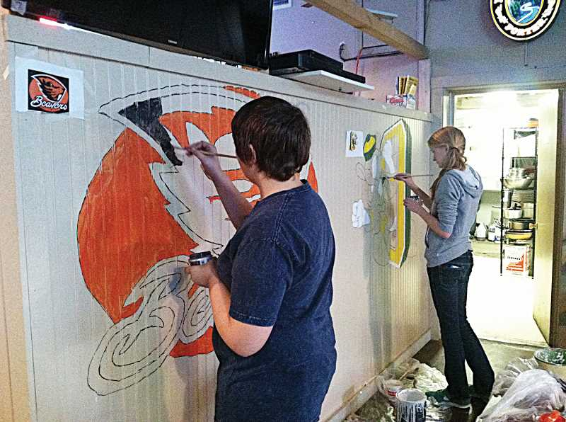 by: PHOTO BY KYLA DANOS - Culver art students Caleb Thompsom and Emma Knepp work on murals at the Desert Inn in Metolius.
