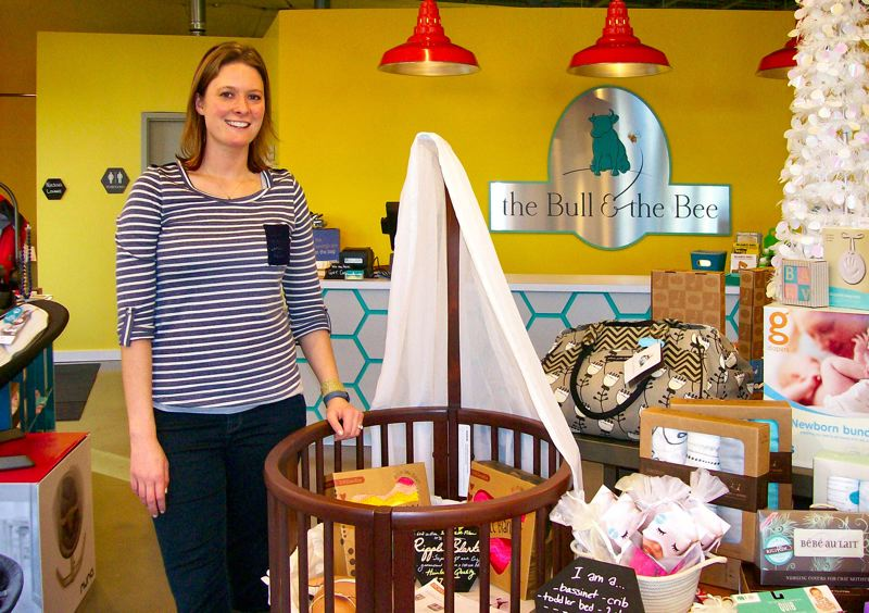 by: RITA A. LEONARD - Barb Wright, owner of the new Westmoreland baby boutique The Bull & The Bee, displays a wooden Stokke bassinet that converts into a sleep system as baby grows older.