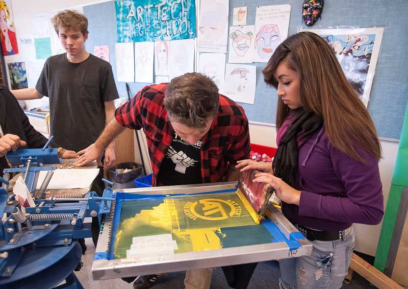 by: PAMPLIN MEDIA GROUP: JOSH KULLA - Teacher Ben Whitcomb coaches Esthela Rodriguez through the screen-printing process.