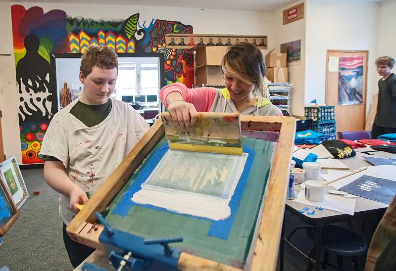 by: PAMPLIN MEDIA GROUP: JOSH KULLA - Alek Newton, left, and Maria Alexandre work together to screen-print an ATHS design onto a shirt.
