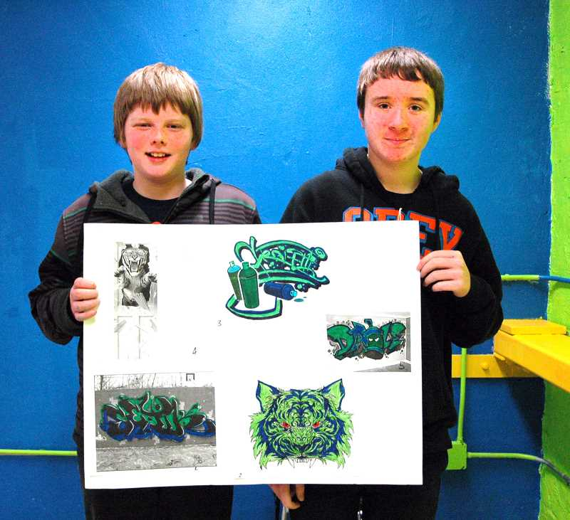 by: ISABEL GAUTSCHI - Seventh-graders Jacob Walton and Tristan McNemar hold up the design scheme they came up with for Estacada Junior High School's game room.