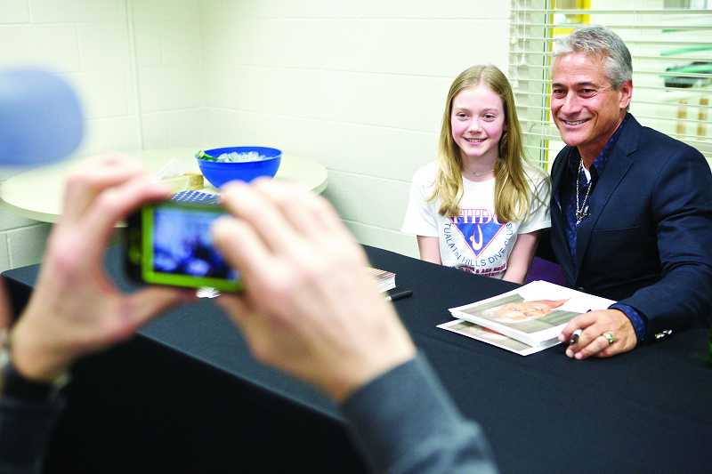 by: TIMES PHOTO: JAIME VALDEZ - Cydney Fellows,12, of Beaverton has her picture taken with Olympic gold medalist Greg Louganis by her dad, John, at the Tualatin Hills Aquatic Center.