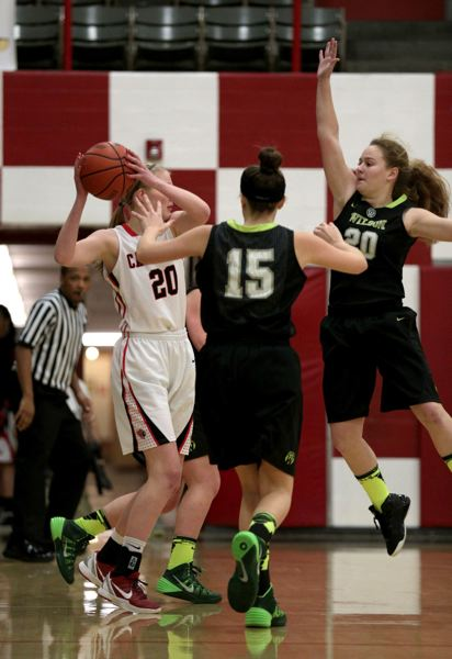 Wilson's Madison Horn (right) jumps to block a pass by Lincoln's Hailey McPhee.