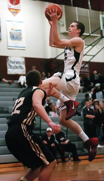 by: DAN BROOD - FLYING -- Sherwood High School junior Ben Milligan (right) goes up to the basket over Milwaukie's Vasilly Voznyuk in Tuesday's game.