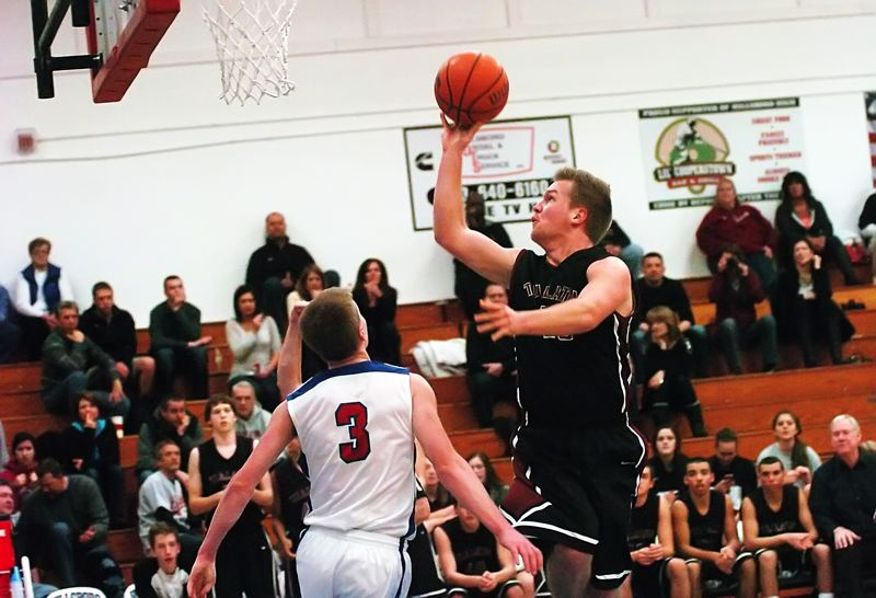 by: DAN BROOD - TO THE HOOP -- Tualatin High School senior Brandon Shroyer (right) goes up to the basket against Hillsboro's Tyler Fernstrom in Friday's game. Shroyer had a big game on defense for the Wolves.